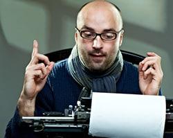 Man typing his favorite writing quotes on typewriter.